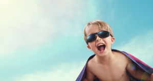 Boy wrapped in beach towel in summer sunshine Stock Photo