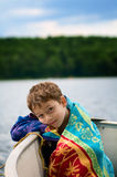 Boy wrapped in a towel in a boat royalty free stock images