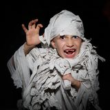 Boy wrapped in white bandages, like an Egyptian mummy, make faces on a black background.  royalty free stock images