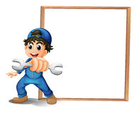A boy with a wrench in front of the empty wooden board Royalty Free Stock Image