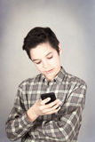 Boy write message. Boy writing message on mobile phone Stock Image