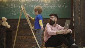 Boy writes with chalk on a board. Lovely toddler boy drawing on chalkboard on wooden background. Man controls learning. Process. Boy learns arithmetic under the stock video