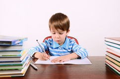 Boy writes in exercise book. Little boy sits at his desk and carefully writing in exercise book. boy 5 years. on the desk a lot of books. photo taken on a light Stock Photography