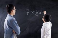 Boy writes multiplication formula Royalty Free Stock Images
