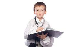 Boy writes in a notebook. Small boy writes in a notebook Stock Photography