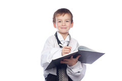 Boy writes in a notebook. Small boy writes in a notebook Stock Photo