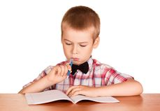 Boy writes in notebook, sitting at Desk isolated on white. Background Royalty Free Stock Photos