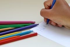 A boy writes on a page with a colored pencils stock image