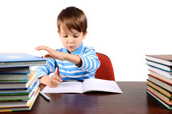 Boy writes and takes a book at the same time. Boy is 5 years. isolated on white Stock Image