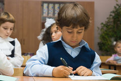 The boy writes to writing-books. The schoolboy at a lesson sits at a school desk and writes to writing-books Stock Images