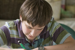 Boy writing. A boy hardly solving homework Stock Photos