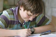 Boy writing. A boy hardly solving homework Royalty Free Stock Photography
