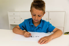Boy writing the ABC alphabet Stock Images