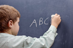 Boy writing alphabet. On chalkboard Stock Images