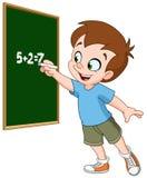 Boy writing on blackboard. School boy writing with chalk on a blackboard Royalty Free Stock Images