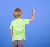 Boy writing on the blue backgroung Stock Images