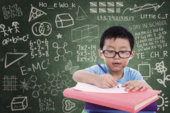Boy writing on book in classroom Royalty Free Stock Photo