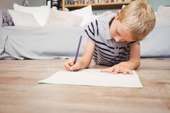 Boy writing in book while lying on hardwood floor at home. Close-up of boy writing in book while lying on hardwood floor at home Royalty Free Stock Image