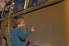 Boy writing on a car. Stock Photo