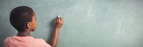 Boy writing with chalk on greenboard in school. Rear view of boy writing with chalk on greenboard in school stock photos