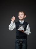 Boy writing with chalk and keeping house model Royalty Free Stock Photos
