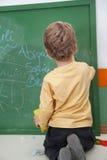 Boy Writing On Chalkboard At Kindergarten. Full length rear view of boy writing on chalkboard at kindergarten Stock Images
