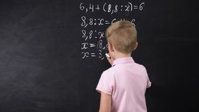 Boy writing on chalkboard math equation, solving exercise, education reform. Stock footage stock video