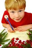 Boy writing Christmas wishes stock photos