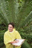 Boy Writing On Clipboard By Large Fern Stock Photography