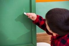 Boy Writing On Green Chalkboard In Preschool. Little boy writing on green chalkboard in preschool stock images