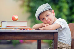 Boy, writing his homework from school, drawing and writing in hi Stock Images