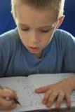 Boy writing homework stock images