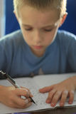 Boy writing homework. Little boy writing homework royalty free stock image