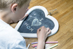 Boy writing I love mom Stock Photo