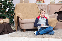 A boy writing a letter to Santa Claus. At Christmas time Royalty Free Stock Photos