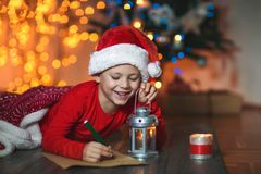 Boy writing letter to Santa Claus in red hat. Near the Christmas tree Stock Photos