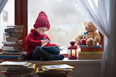 Boy, writing letter to Santa. On the window, teddy bear and books around him Royalty Free Stock Photography