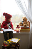 Boy, writing letter to Santa. On the window, teddy bear and books around him Stock Photo