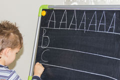 Boy writing letters learning procces son smart child Royalty Free Stock Image