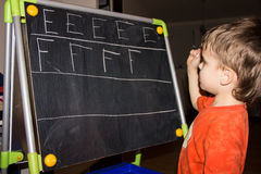 Boy writing letters learning process knowledge of small child Stock Photos