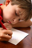 Boy writing note letter to santa Stock Photos