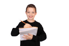 Boy writing in notebook Stock Image