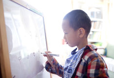 Boy writing number on the white board Royalty Free Stock Images