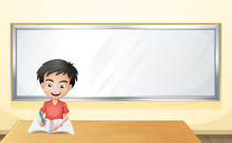 A boy writing on a paper with a blank board Royalty Free Stock Photos