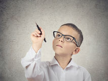 Boy writing with a pen on blackboard. Closeup portrait happy boy, little man, student with glasses writing with pen on blackboard, isolated grey wall background stock photos