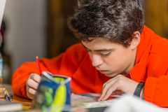 Boy writing with red and blue pencil. Caucasian boy doing homeworks writes with red and blue pencil Royalty Free Stock Photo