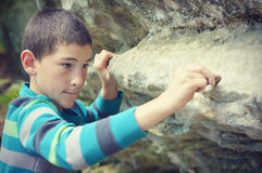 Boy Writing on Rock with a Stone Royalty Free Stock Photography