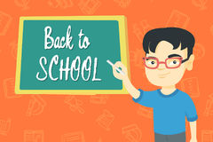 Boy writing text back to school on the blackboard. Happy asian schoolboy writing text back to school on the classroom blackboard. Smiling schoolboy in glasses Stock Photos