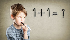 Boy, writing and thinking, trouble with math Stock Image