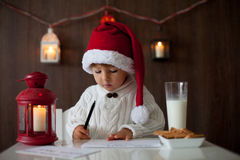 Boy, writing to Santa. Little cute boy, writing to letter to Santa Claus, sitting at home, drinking milk Stock Image